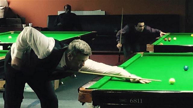 Round of 16 action at the 2015 United States National Snooker Championship, with Ian O'Mahony down at the table, while in the background, Vaishal Talati contemplates his next shot - Photo © SnookerUSA.com